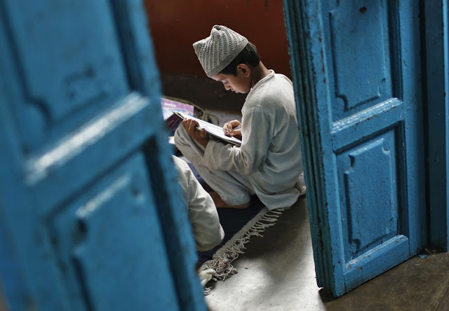 A Muslim boy learns to read the Koran at a madrassa, or religious school, during the holy month of Ramadan in the old quarters of Delhi July 31, 2013